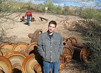 Austin standing by some old train wheels.