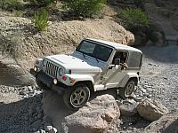 Carl Hoff drives his jeep over a rock in Box Canyon.